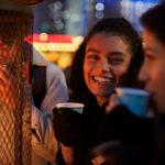 Zwei Freundinnen trinken Glühwein auf dem Weihnachtsmarkt während sie ihr JGA Musikvideo filmen