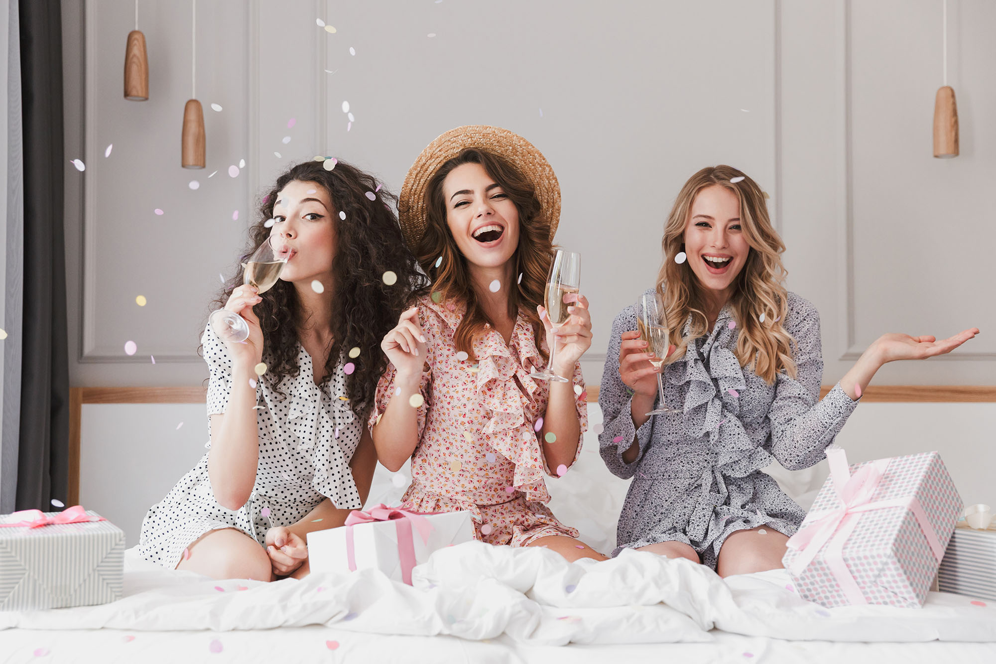 Drei junge Frauen sitzen auf dem Bett, trinken Sekt und werfen Konfetti. Es ist eine Jungegesellenabschiedsparty